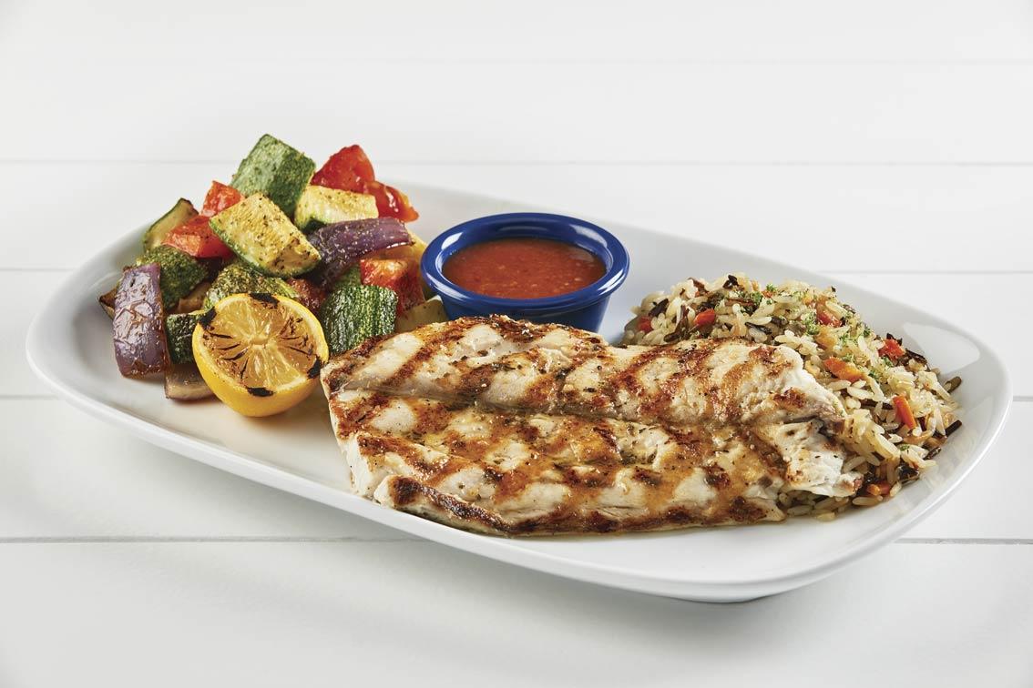 Es un pescado cocinado con guarnición de patatas y verduras.